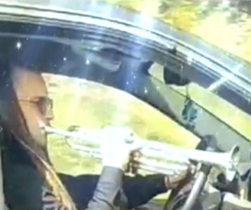 Driver plays trumpet behind the wheel on busy highway