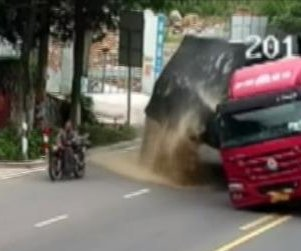 Lucky motorcyclist dodges overturning truck on Chinese street
