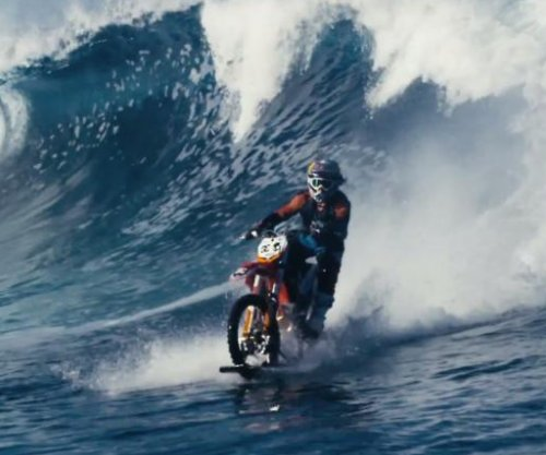 Motocross stunt rider surfs waves on modified dirt bike