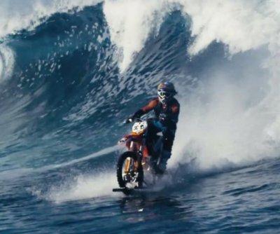 Motocross stunt rider surfs waves on modified dirt bike