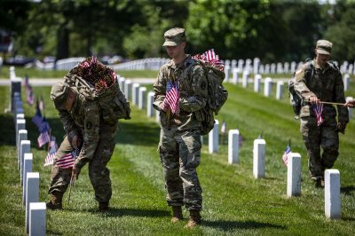 Service members place flags at at Arlington National Cemetery