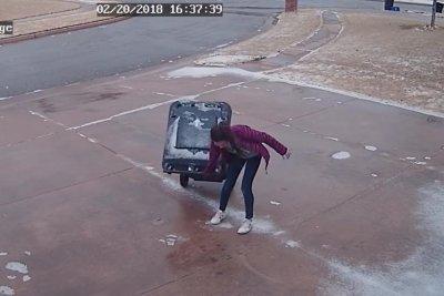 Oklahoma girl bringing in trash bin struggles on icy driveway