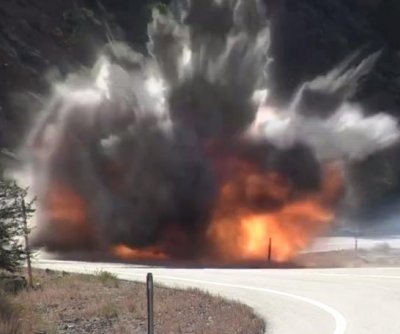 Workers use explosives to remove boulders from a California mountain road