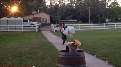 Groom carries bride, falls on top of her
