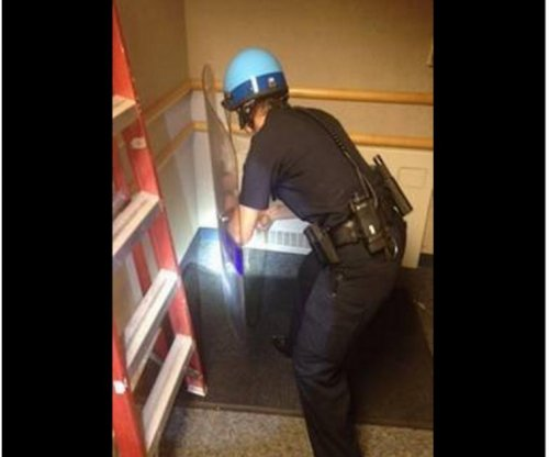 Police officer in riot gear takes on black widow spiders