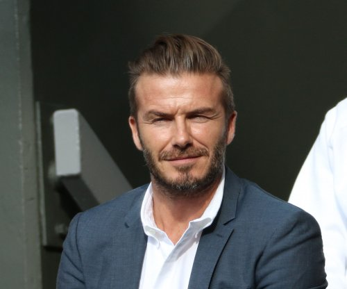 David Beckham catches tennis ball during Wimbledon match