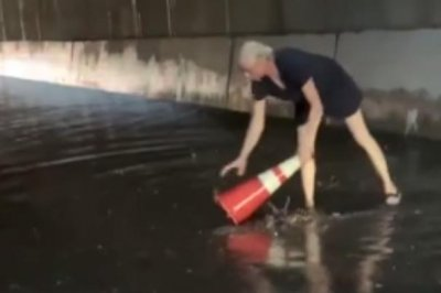 Woman uses traffic cone to clear drains on flooded New York road