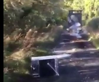 Cyclist films truck losing load of trash in the road