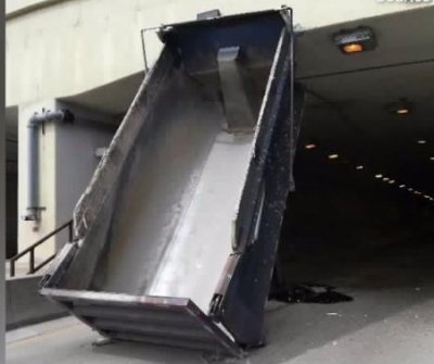 Dump truck with raised bed collides with highway overpass