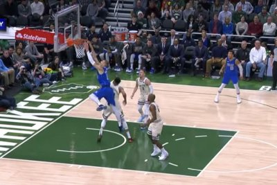 Mavericks' Kristaps Porzingis dunks on top of Giannis Antetokounmpo