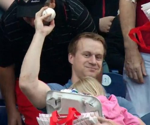 Dad calmly catches foul ball one-handed while holding his daughter