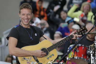 Chris Martin performs with children Apple and Moses