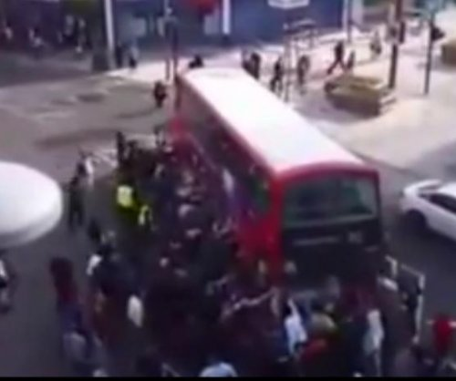 Londoners lift bus to free pinned unicyclist