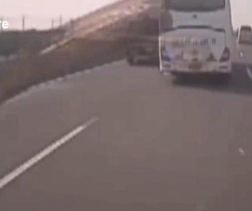 Airborne wood smashes bus windshield on highway