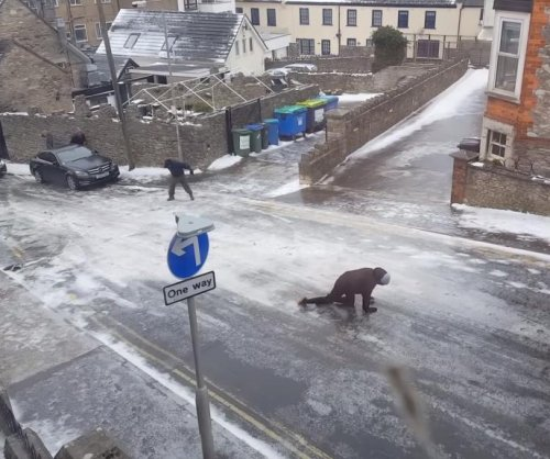 Britons struggle to walk up road's icy hill