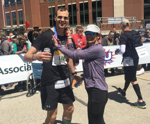 Man carries 100 pounds to break marathon running record