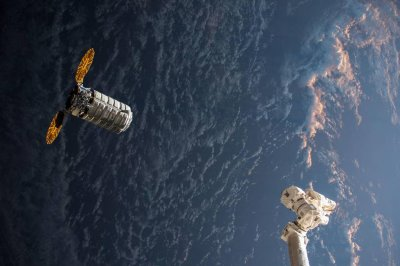 Sunrise colors space station image of approaching cargo ship