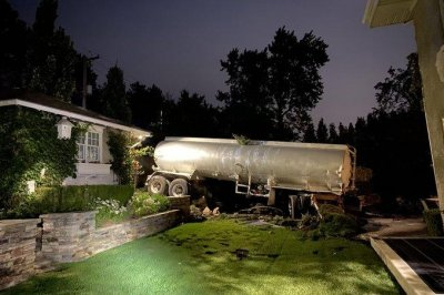Runaway oil tanker trailer crosses road, ends up in back yard