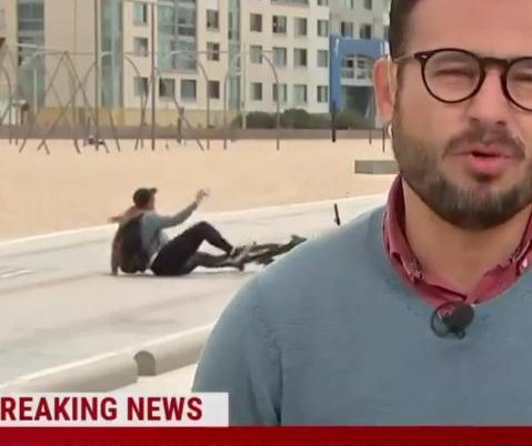 Selfie-taking cyclist wipes out in background of live news broadcast