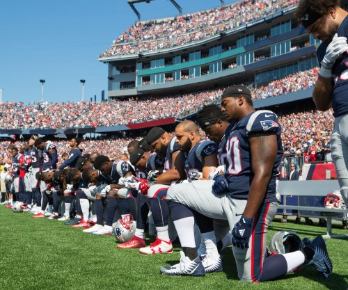 Boos ring out as sixteen New England Patriots kneel for anthem; Houston Texans lock arms