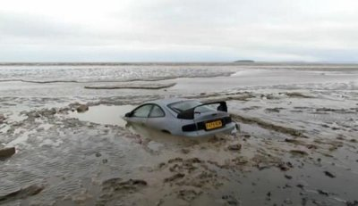 Sports car sinks during mudflats drive
