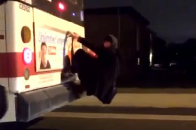 Man clings to the back of moving city bus in Toronto