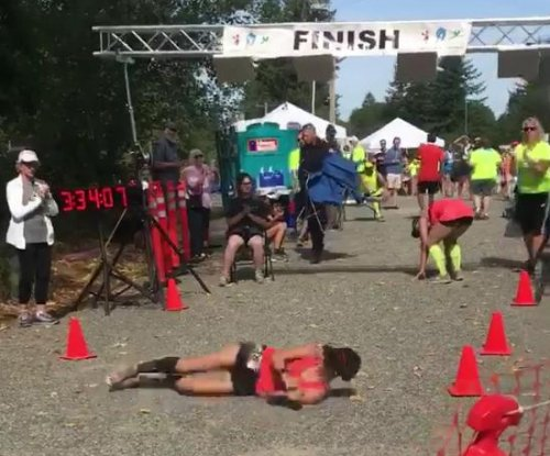 Marathon runner takes a fall, rolls across the finish line