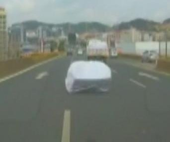 Driver swerves to avoid couch falling from truck on the highway