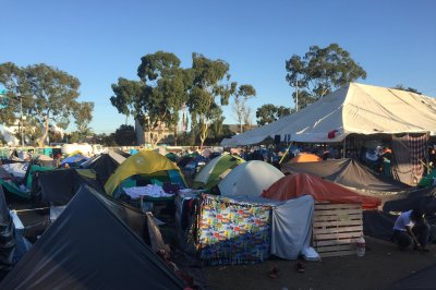 Subdued migrants at Tijuana border camp consider options