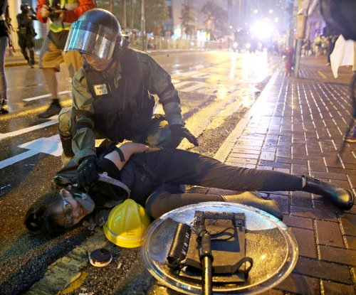Police draw guns, fire water canons on Hong Kong protesters