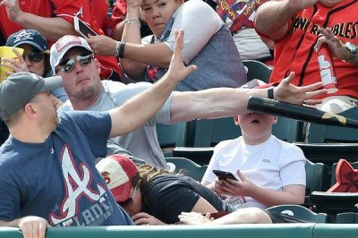 Fast-acting dad deflects baseball bat headed for son's face
