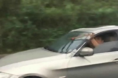 Man uses dowel to operate broken windshield wipers
