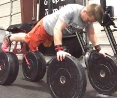 Bodybuilder does push-ups while balancing on weights