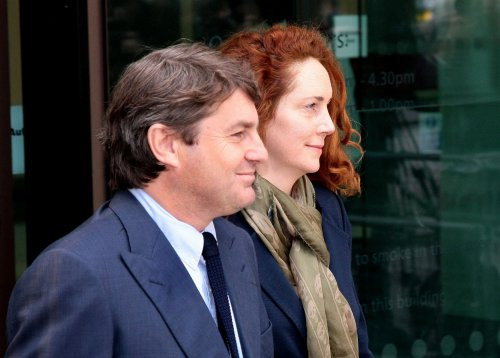 Charges leveled against 8 in phone-hacking