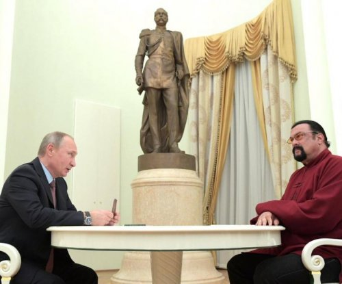 President Vladimir Putin presents Steven Seagal with Russian passport