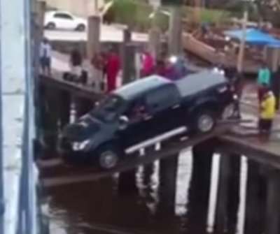 Pickup truck drives across wooden planks to board ferry