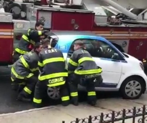 New York City firefighters lift car out of their way