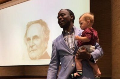 Professor gives lecture while holding student's infant