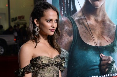 Alicia Vikander wears gold gown to 'Tomb Raider' premiere