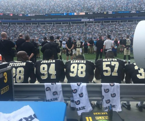 New Orleans Saints players take seats on bench during anthem vs. Carolina Panthers