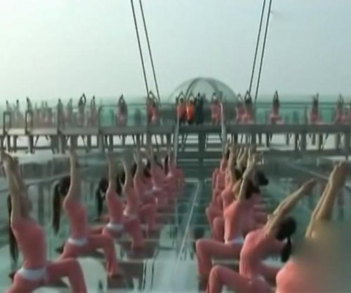 More than 150 women perform synchronized yoga on glass platform
