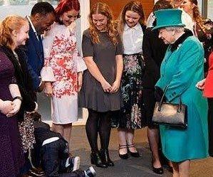 Overwhelmed boy crawls away from Queen Elizabeth