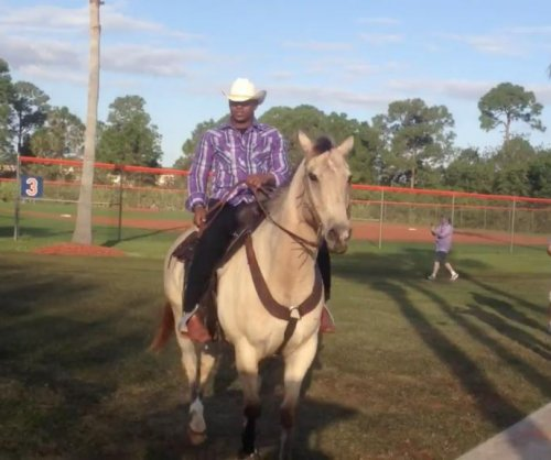 New York Mets OF Yoenis Cespedes arrives on horseback