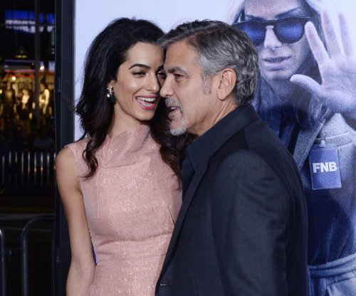 George Clooney, wife Amal share intimate kiss at 'Our Brand is Crisis' premiere