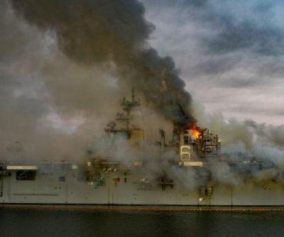 Helicopter water drops help fight fire on still-burning USS Bonhomme Richard