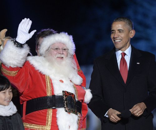 Obamas send holiday greetings; first lady helps track Santa