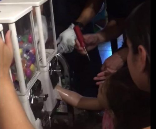 Paramedics free young girl's arm from gumball machine