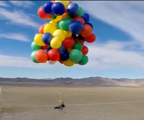 Man parachutes from balloon-lifted lawn chair
