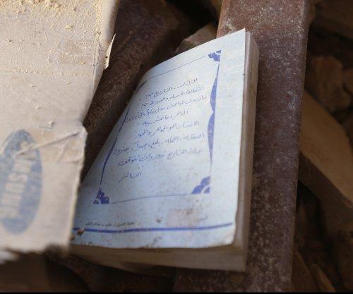 Volunteers scavenge for books beneath the rubble in Daraa, Syria