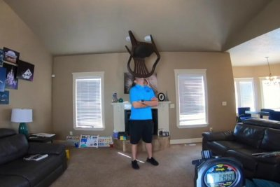 Idaho man balances chair on chin for over an hour to break world record